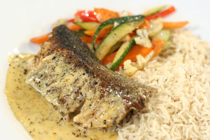 Black cod served with rice and vegetables.