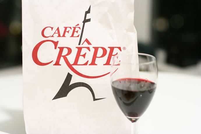 Cafe Crepe logo on a take-out bag with a glass of wine.