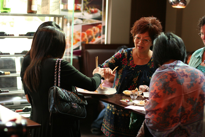 Asian ladies wearing fancy dresses, eating sushi at the standup reception at Irashai Grill.