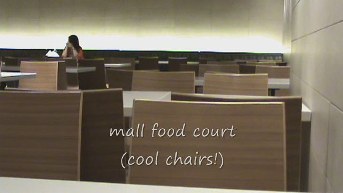The food court has sleek, modern decor with cool lighting and neat chairs.