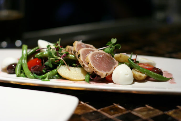 The entree sized version of the salad, La Petite Salad Niçoise, with fresh micro greens, quail eggs, haricot vert niçoise olives, fingerling potato, seared albacore tuna
